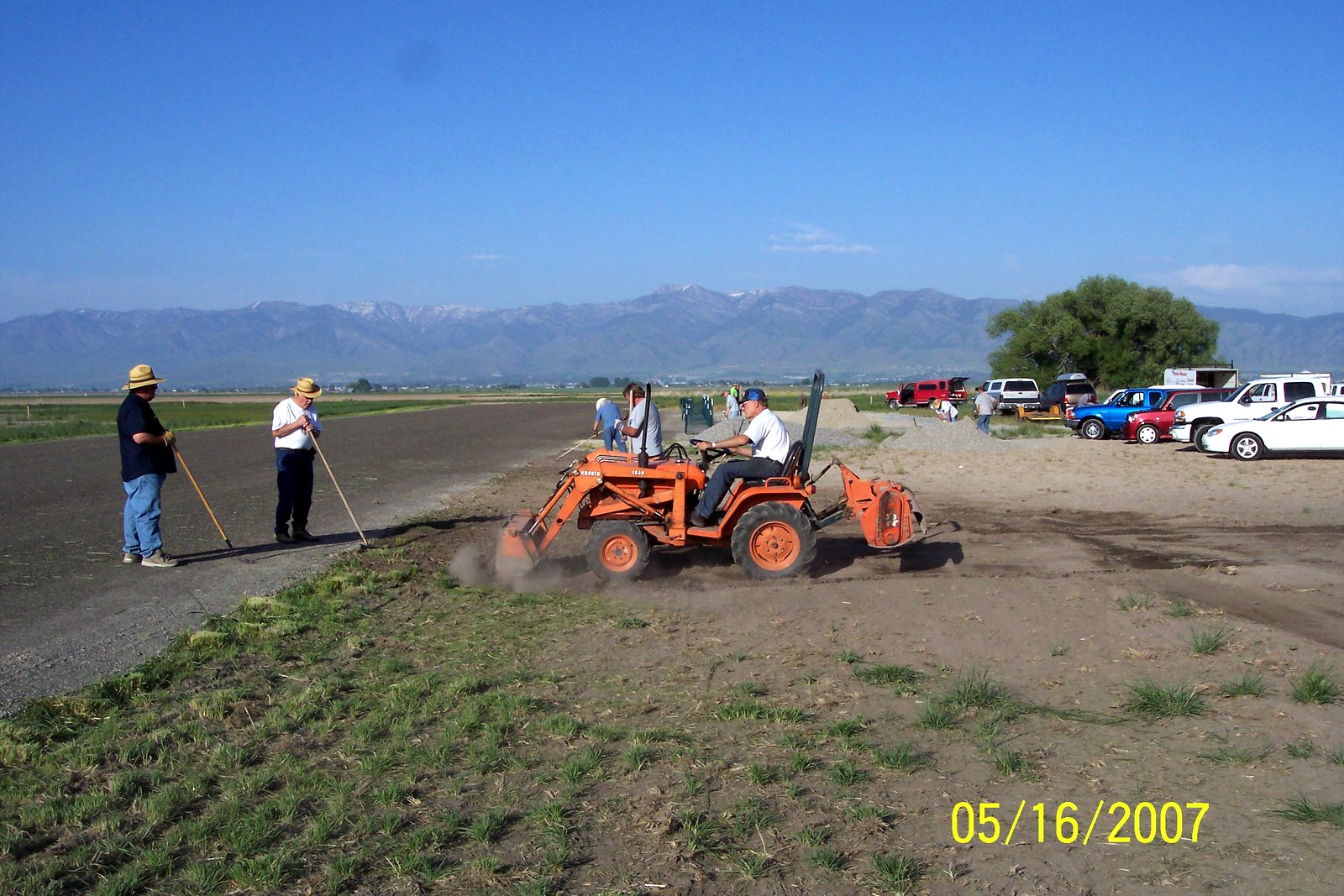 DEL BULLEN BEGINS TAPERING RUNWAY EDGES. MICHAEL SMITH, NATE FREIDLI AND RICK JENSEN DO THE RAKING.