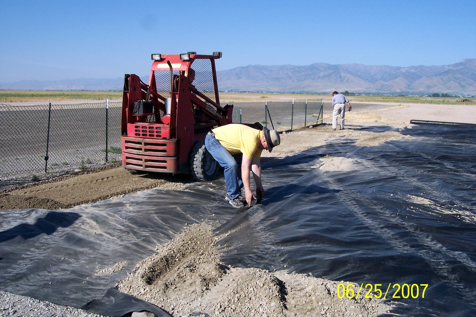 WEED BARRIER MATERIAL IS ADJUSTED BY VERN SMITH.