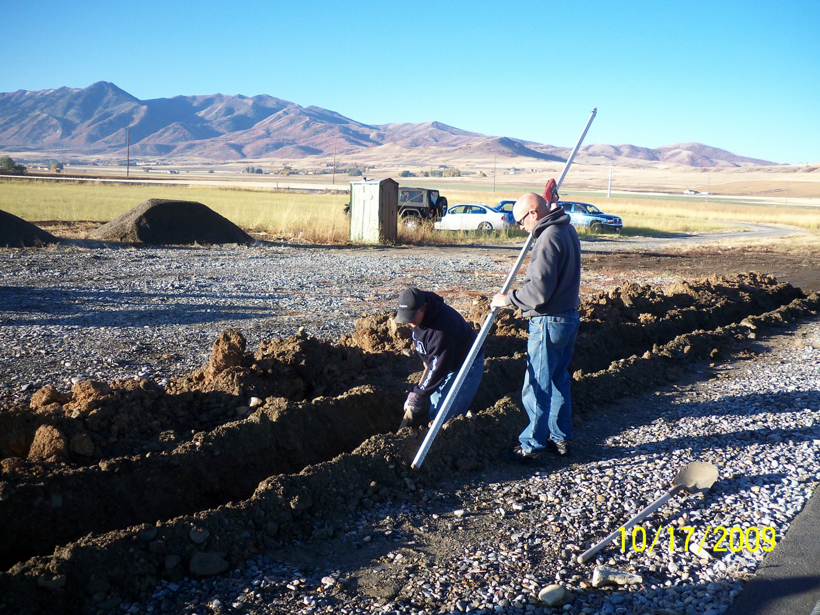 KEITH MERRILL WORKS LEVELING TRENCH BASE AS JERRY COKELY ASSISTS WITH LAZER TRANSIT ROD.