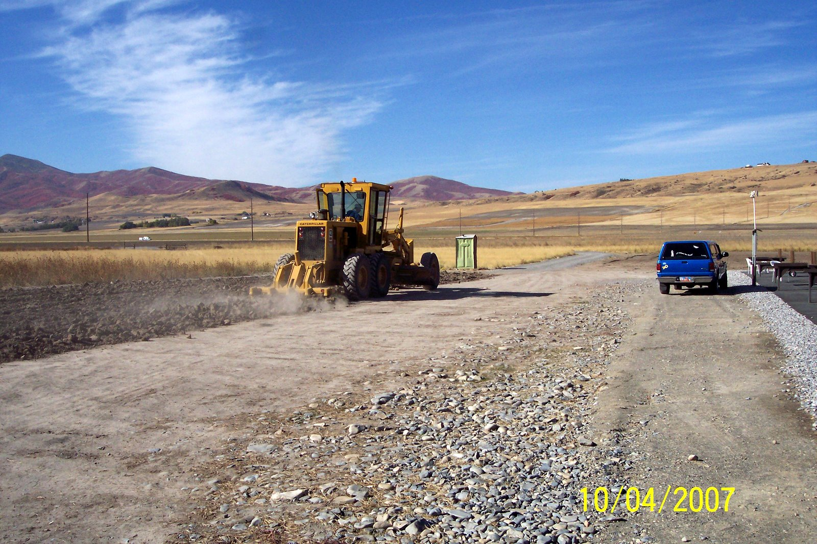 FARMER LARRY ROUNDY WORKS OVER THE PARKING AREA.