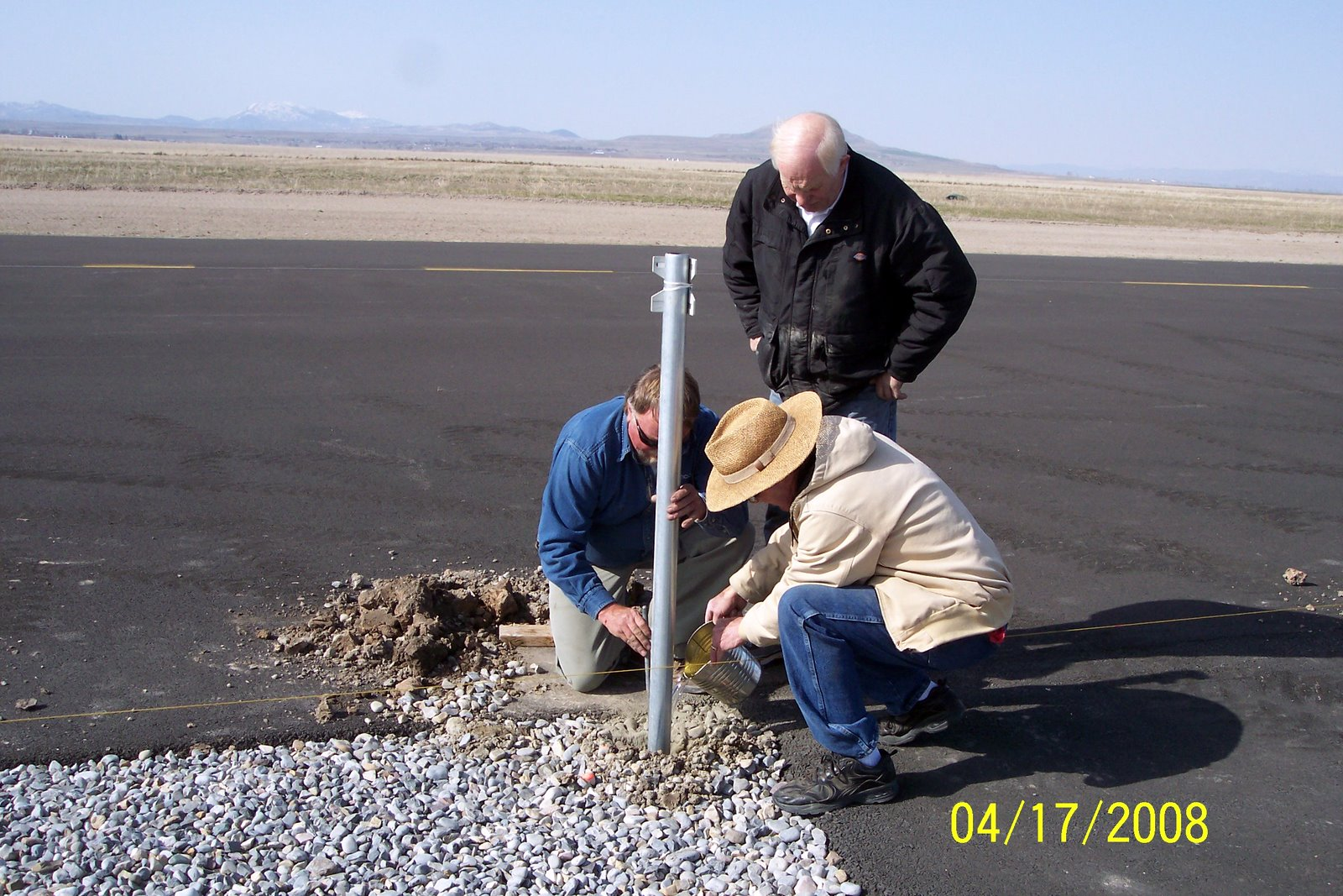 CEMENT FOR THE FIRST SAFETY FENCE POST. RICK JENSEN, JERRY COKELY, VERN SMITH.