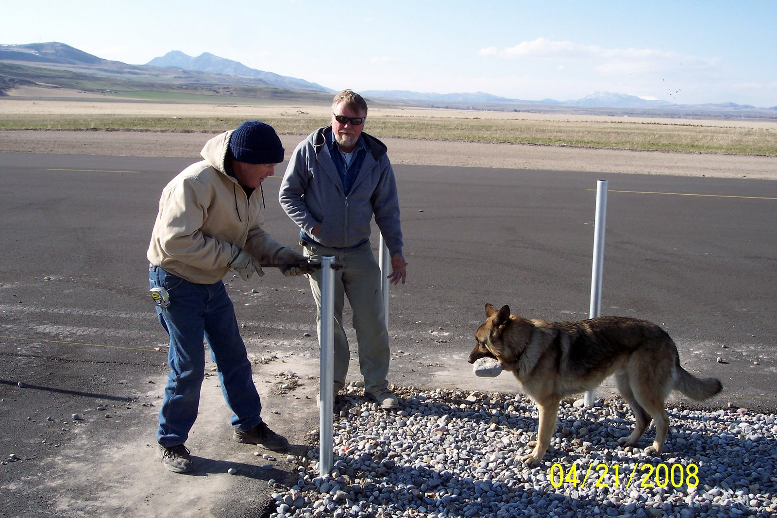 "JERRY COKELY AND RICK JENSEN (ASSISTED BY ""SPUD"" , VERN SMITH'S GERMAN SHEPARD) WORK ON SAFETY FENCE."