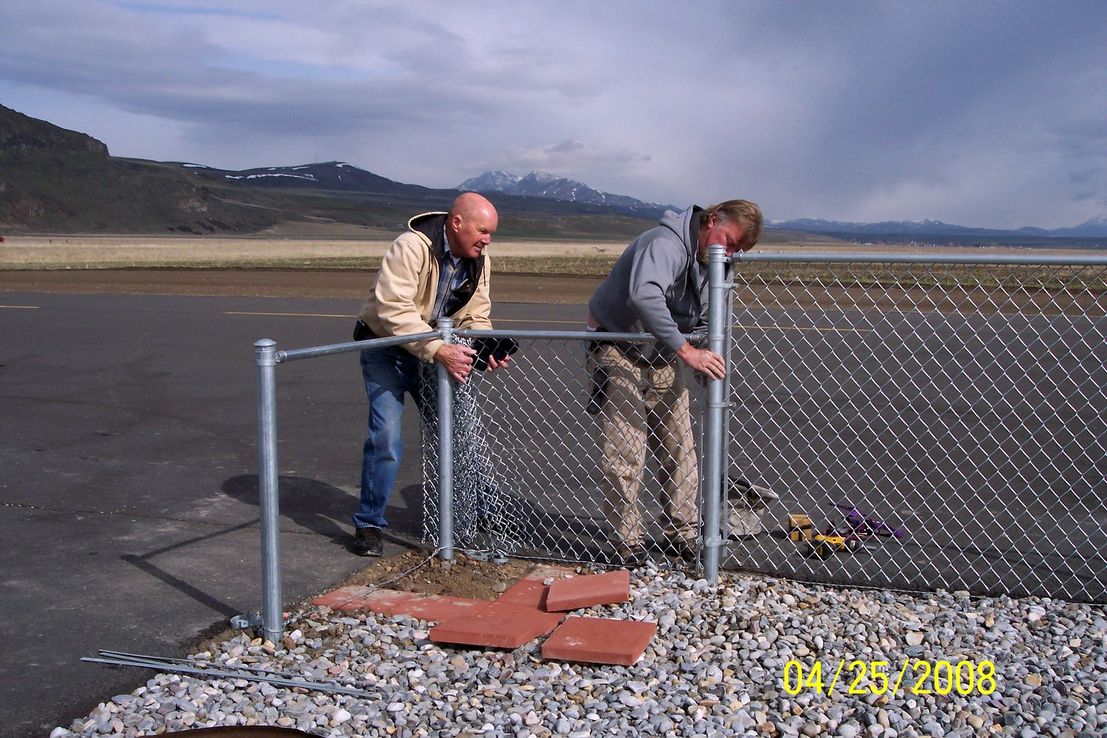 JERRY COKELY AND RICK JENSEN STRETCHING FENCE FABRIC.