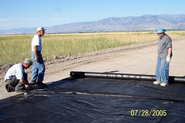 IVAN HOOLEY, DEL BULLEN AND WINSTON REESE ROLLING OUT WEED BARRIER MATERIAL.