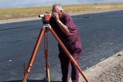 BRCC RESIDENT SURVEYOR AND ARCHITECT, GENE HAYCOCK SHOOTS GRADE FOR RUNWAY.