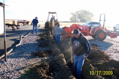 KEITH MERRILL AND AARON BLIESNER DOWN IN THE TRENCHES. RON BLIESNER WITH LAZER ROD AND MIKE SPINDLER OPERATES HIS BACKHOE.